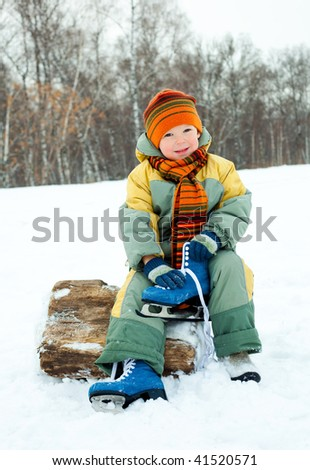 cute little boy wearing warm winter clothes is going to ice skate - stock photo