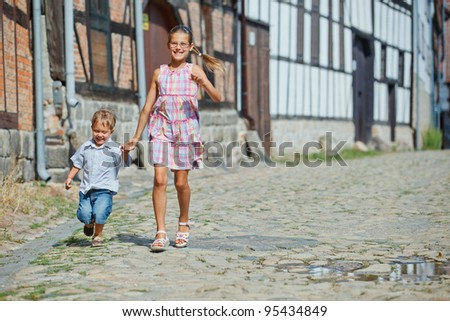 Cute little boy wiht his sister outdoors in city - stock photo