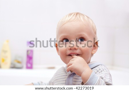 Cute little boy with a finger in his mouth in bathroom