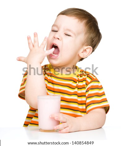 Cute little boy with a glass of milk licking his finger, isolated over white - stock photo