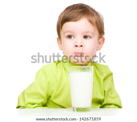 Cute little boy with a glass of milk showing funny grimace, isolated over white - stock photo