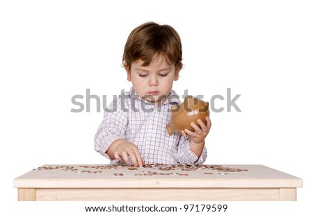 Cute little boy with a piggy bank and some coins on the table. Isolated on white - stock photo