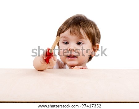 Cute little boy with a screwdriver hidden behind the table. Isolated on white.