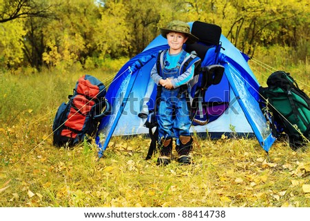 Cute little boy with backpack and tent outdoor. - stock photo