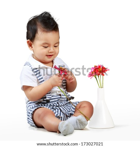 Cute little boy with beautiful flower sitting on floor, Isolated over white