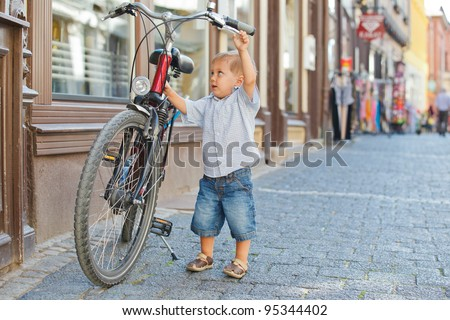 cute little boy with big bike outdoors in city street - stock photo