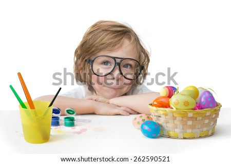 Cute little boy with blonde hair, blue eyes and toy glasses painting easter eggs happy easter banner isolated on white background