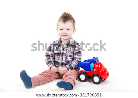 Cute little boy with blue eyes playing with a toy car. Happy kid sitting isolated on white background. - stock photo