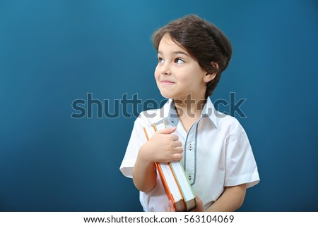 Cute little boy with books on color background