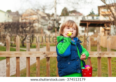 Cute little boy with bucket full of colorful easter eggs - stock photo