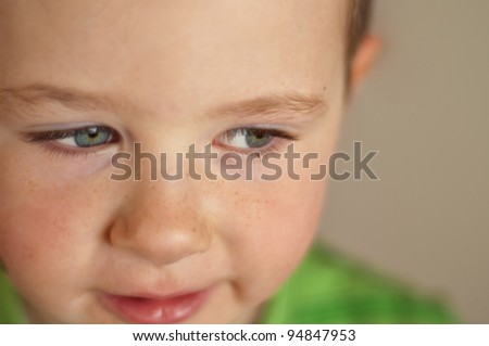 Cute little boy with camera focus on his beautiful clear blue eyes - stock photo
