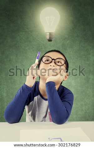 Cute little boy with casual clothes thinking idea while sitting under bright light bulb and holding a pen - stock photo