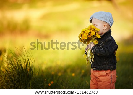 cute little boy with dandelions bouquet