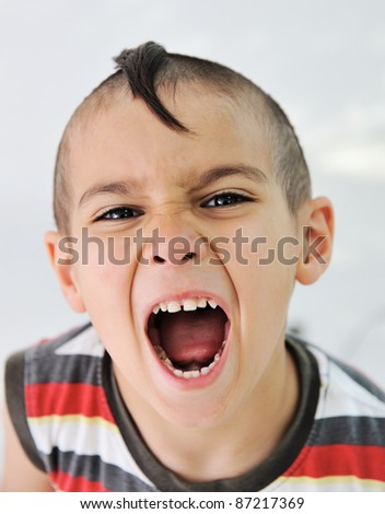 Cute little boy with funny hair and cheerful grimace - stock photo