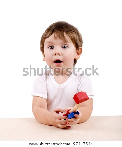 Cute little boy with hand-tools behind the table. Isolated on white. - stock photo