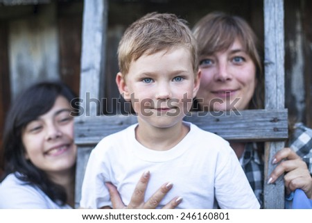 Cute little boy with his mother and older sister in the background.