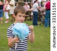 cute little boy with huge blue ball of candyfloss at a local village fete - stock photo