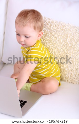 Cute little boy with laptop on sofa at home - stock photo
