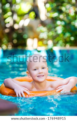 Cute little boy with lifebuoy in swimming pool outdoors - stock photo