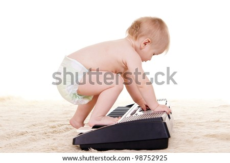 cute little boy with piano on carpet - stock photo