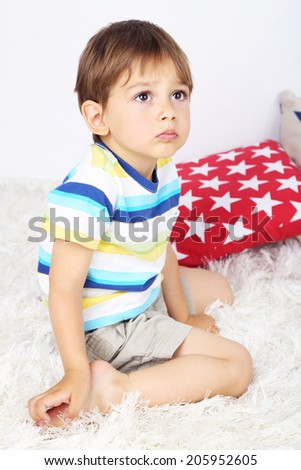 Cute little boy with pillow on floor in room