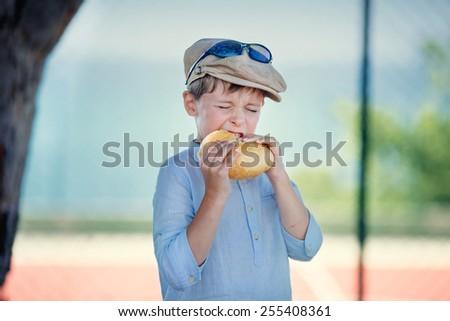 Cute little boy with pleasure eats hamburger outdoors  - stock photo