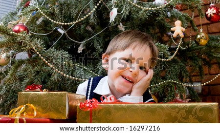 Cute little boy with presents near Christmas tree.