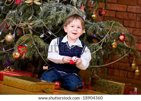 Cute little boy with presents near Christmas tree. - stock photo