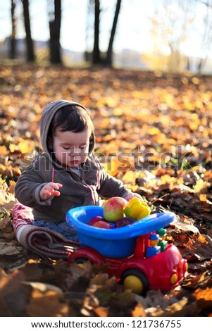 cute little boy with ripe vegetables in autumn park - stock photo