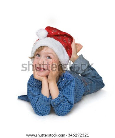 Cute little boy with Santa hat  lying on the floor, looking up isolated on white background