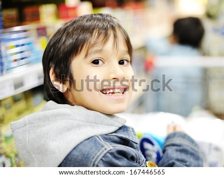 Cute little boy with shopping cart at market