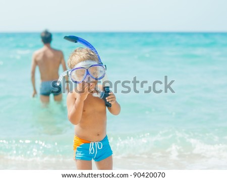 Cute little boy with snorkeling equipment on tropical beach, his father background. - stock photo