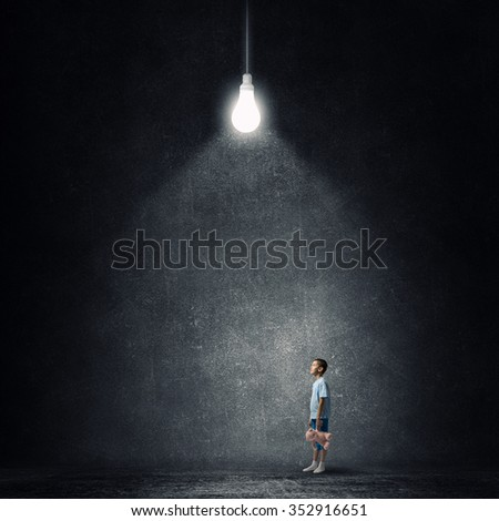 Cute little boy with toy bear in concrete dark room - stock photo