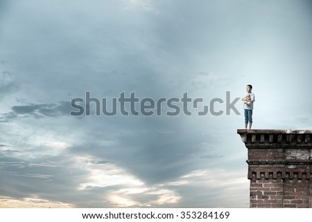 Cute little boy with toy bear on building top - stock photo