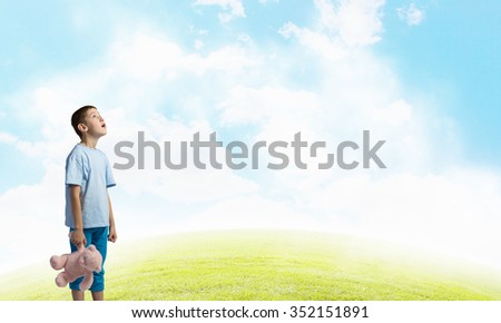 Cute little boy with toy bear on cloud background - stock photo