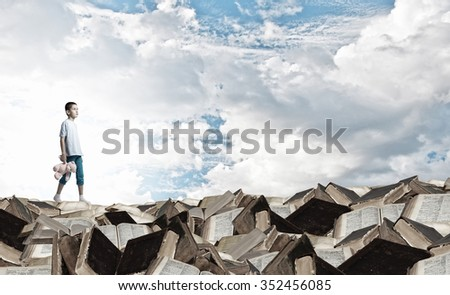 Cute little boy with toy bear on pile of books - stock photo