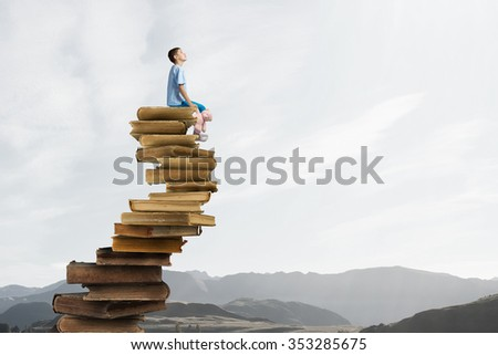 Cute little boy with toy bear sitting on pile of books - stock photo