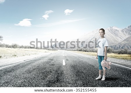 Cute little boy with toy bear standing on asphalt road - stock photo