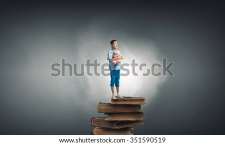 Cute little boy with toy bear standing on pile of books - stock photo
