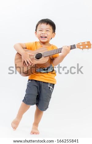 Cute little boy with ukulele guitar - stock photo