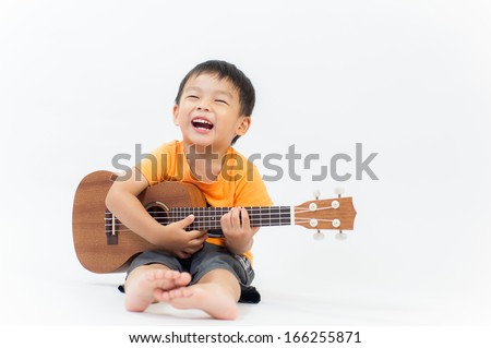 Cute little boy with ukulele guitar - stock photo