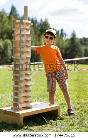 Cute little boy with wooden tower game - stock photo