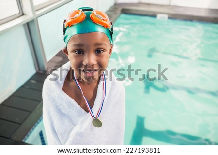 Cute little boy wrapped in towel with medal poolside at the leisure center - stock photo