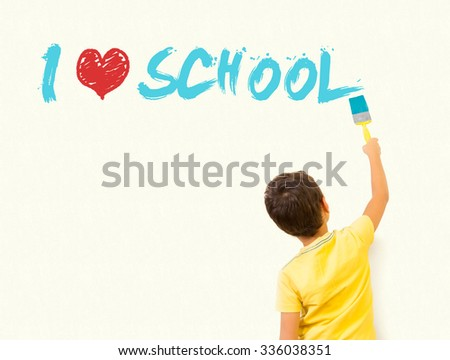 "Cute little boy writing ""I Love School"" with painting brush on wall background - stock photo"