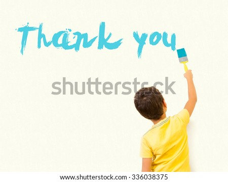 """Cute little boy writing """"Thank You"""" with painting brush on wall background - stock photo"""