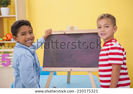 Cute little boys drawing on chalkboard at the nursery school - stock photo