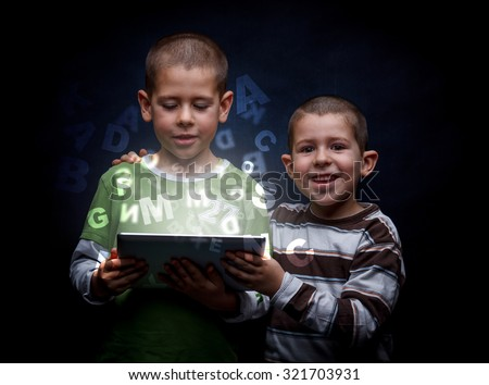 Cute little boys using tablet pc - stock photo
