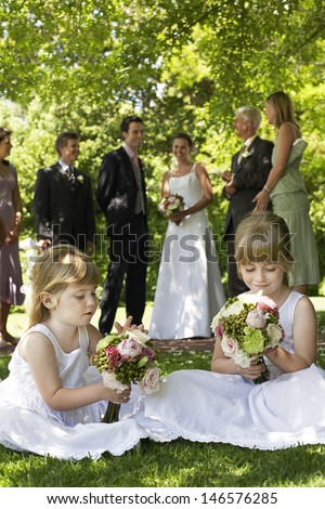 Cute little bridesmaids holding bouquets in lawn with guests and wedding couple in background - stock photo