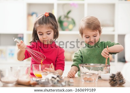Cute little brother and sister baking cookies in the kitchen - stock photo