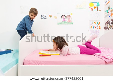 Cute little brother and sister playing in their room - stock photo